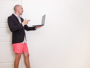 photo of a man wearing a suit jacket with shorts on a video call